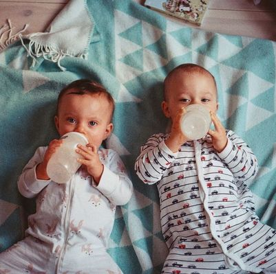 Image to twin babies laying on a blue blanket drinking bottles