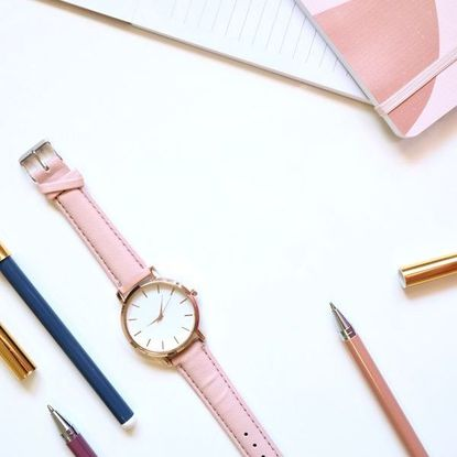 Photo of a pink watch, pens, and a pink notebook.