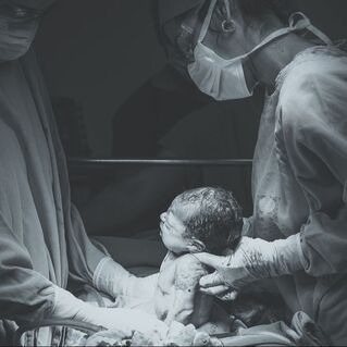 Image of two doctors performing a cesarean birth.  Infant is halfway out of the mother.